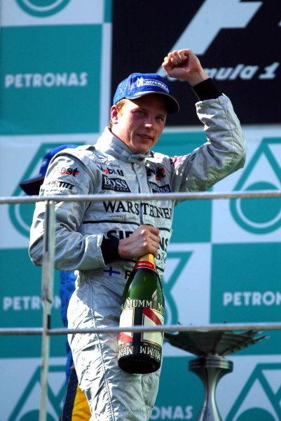 Kimi Raikkonen (FIN) McLaren celebrates on the podium after his maiden GP victory. Formula One World Championship, Rd2, Malaysian Grand Prix, Race Day, Sepang, Malaysia, 23 March 2003. DIGITAL IMAGE