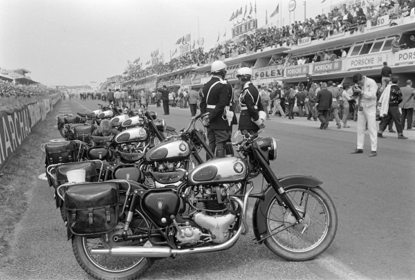 Gendarmes and their motorcycles by the side of the track.