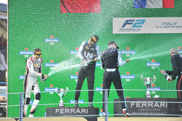 Theo Pourchaire (FRA, ART Grand Prix), 1st position, Guanyu Zhou (CHN, Uni-Virtuosi Racing), 2nd position, and Christian Lundgaard (DNK, ART Grand Prix), 3rd position, spray champagne on the podium