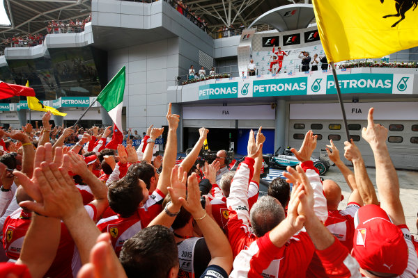 Sepang International Circuit, Sepang, Kuala Lumpur, Malaysia. Sunday 29 March 2015. Sebastian Vettel, Ferrari, 1st Position, arrives on the podium to the cheers of his Ferrari team. World Copyright: Andrew Hone/LAT Photographic. ref: Digital Image _ONY1016