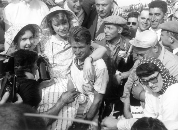 1956 French Grand Prix.Reims-Gueux, France. 1 July 1956.Peter Collins (Lancia-Ferrari) enjoys the spoils of victory. 1st position. Portrait.World Copyright: LAT PhotographicRef: black & white exhibition A022/MotorSport calendar