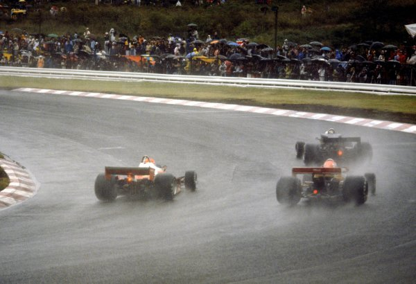 Niki Lauda (AUT) Ferrari 312T2 (Left) is passed in the appalling wet conditions by sixth placed Gunnar Nilsson (SWE) and ninth placed GP debutante Noritake Takahara (JPN) Surtees TS19, shortly before withdrawing from the race at the end of lap two because of the poor weather conditions. Japanese Grand Prix, Rd 16, Fuji, Japan, 24 October 1976. BEST IMAGE