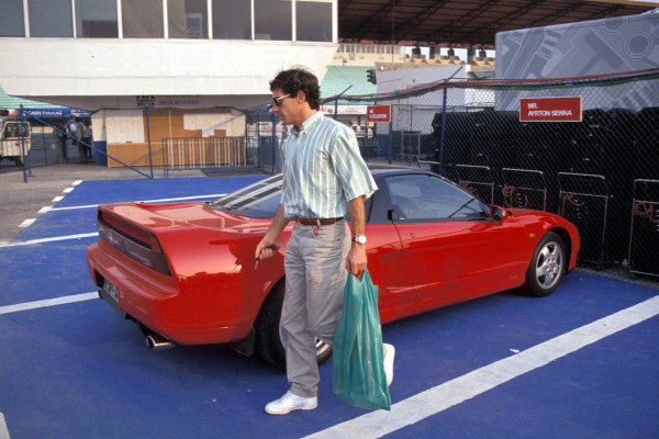 Ayrton Senna walks past a Honda NSX