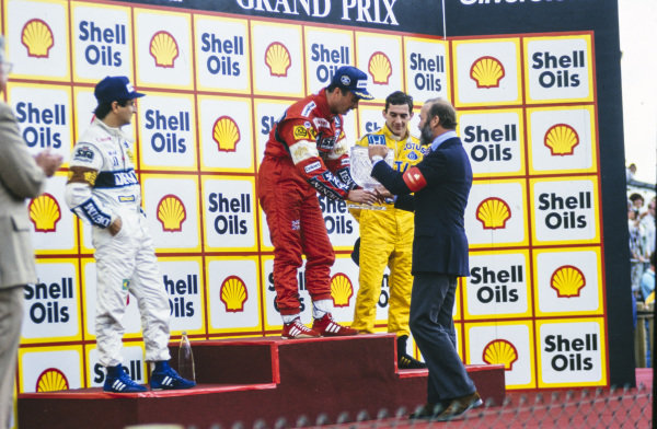 Nigel Mansell, 1st position, receives his trophy from Prince Michael of Kent. He is on the podium with Nelson Piquet, 2nd position, and Ayrton Senna, 3rd position.