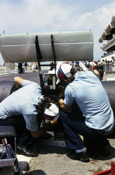 Mechanics work on the rear of one of the Brabham BT44B Ford cars in the pitlane.