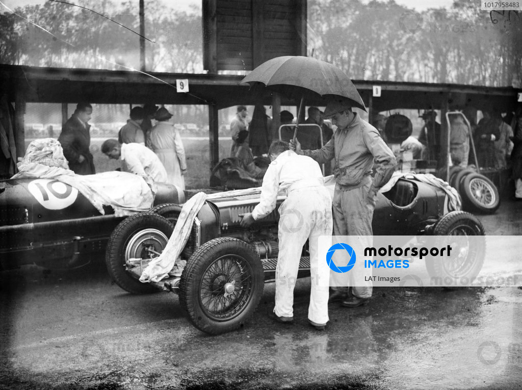 A mechanic replaces the bonnet on Dick Shuttleworth's Alfa Romeo Tipo B/P3 while another mechanic holds an umbrella over him.