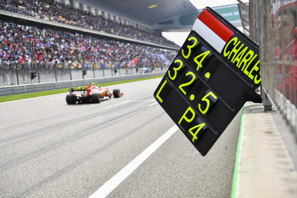 A team member pulls in the pit board after Charles Leclerc, Ferrari SF90, passes