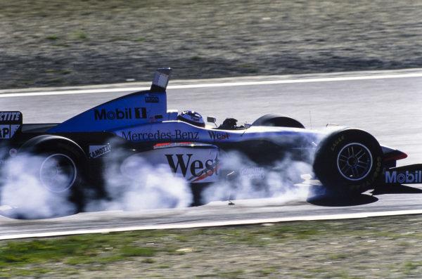Mika Häkkinen, McLaren MP4-12 Mercedes, locks up.