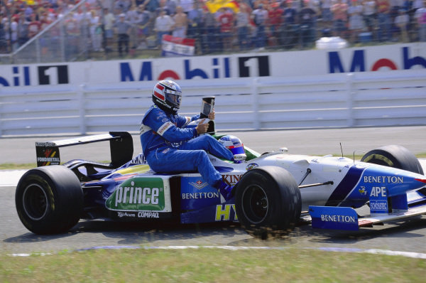 Jean Alesi gives team mate Gerhard Berger a lift back to the pits on his Benetton B196 Renault.