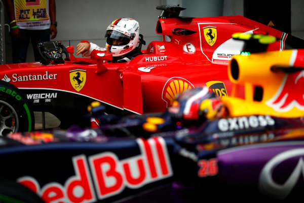 Sepang International Circuit, Sepang, Kuala Lumpur, Malaysia. Saturday 28 March 2015. Sebastian Vettel, Ferrari, and Daniil Kvyat, Red Bull Racing, arrive in Parc Ferme. World Copyright: Andrew Hone/LAT Photographic. ref: Digital Image _ONZ9868