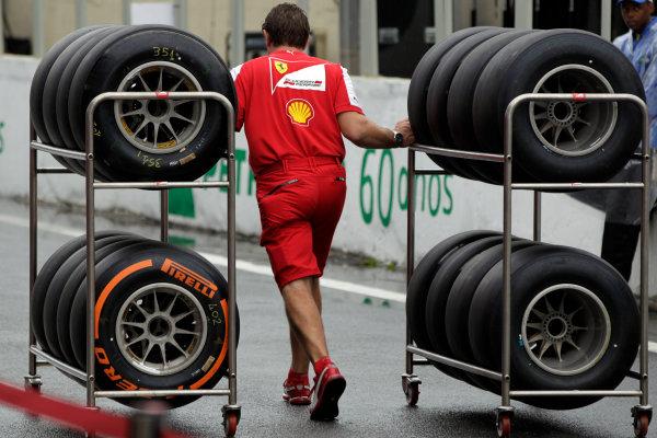 Interlagos, Sao Paulo, Brazil. Friday 22nd November 2013.  A Ferrari mechanic hauls some tyres. World Copyright: Andy Hone/LAT Photographic. ref: Digital Image _ONY8565