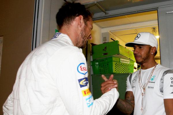 Yas Marina Circuit, Abu Dhabi, United Arab Emirates. Sunday 27 November 2016. Jenson Button, McLaren, says goodbye to former team mate Lewis Hamilton, Mercedes AMG. World Copyright: Charles Coates/LAT Photographic ref: Digital Image DJ5R0289