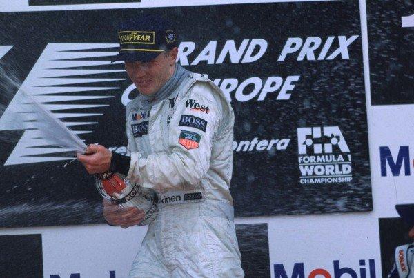 1997 European Grand Prix.Jerez, Spain.24-26 October 1997.Mika Hakkinen (McLaren Mercedes) celebrates his 1st position and maiden Grand Prix win on the podium.World Copyright - LAT Photographic