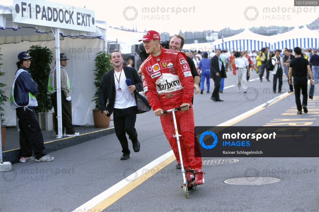 Michael Schumacher zips his way through the paddock on his scooter.