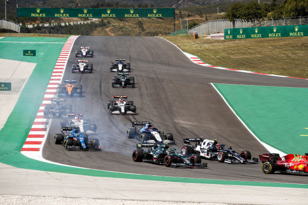 Charles Leclerc, Ferrari SF21, leads Pierre Gasly, AlphaTauri AT02, Sebastian Vettel, Aston Martin AMR21, George Russell, Williams FW43B, Fernando Alonso, Alpine A521, and the remainder of the field at the start