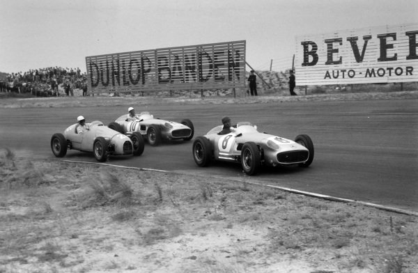 Juan Manuel Fangio, Mercedes W196, leads as Robert Manzon, Gordini T16, battles with Stirling Moss, Mercedes W196, behind.