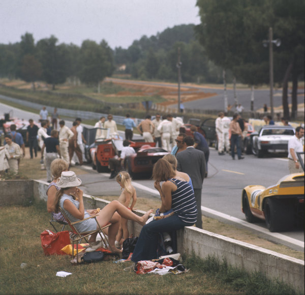 A family sits beside the track during filming of the Steve McQueen movie Le Mans. David Piper's Porsche 917, a Porsche 914, Lola T70 and a Chevron are visible