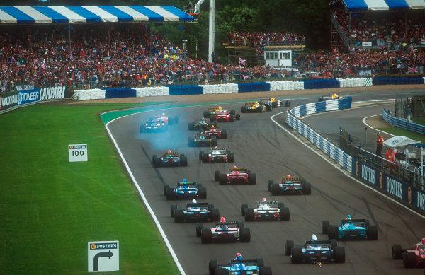 1992 British Grand Prix.Silverstone, England.10-12 July 1992.Riccardo Patrese beats poleman and teammate Nigel Mansell (both Williams FW14B Renault's) around Copse at the start, followed by Martin Brundle, Michael Schumacher (both Benetton B192 Ford's), Ayrton Senna, Gerhard Berger (both McLaren MP4/7A Honda's), Johnny Herbert (Lotus 107 Ford), Erik Comas (Ligier JS37 Renault), Jean Alesi (Ferrari F92A) and Mika Hakkinen (Lotus 107 Ford).Ref-92 GB 10.World Copyright - LAT Photographic