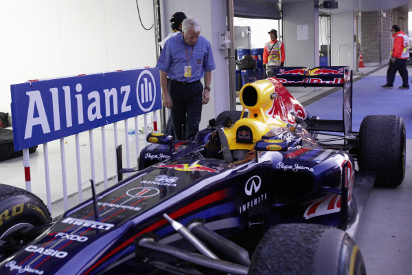 Charlie Whiting has a look at Sebastian Vettel's Red Bull RB7 Renault after the race.