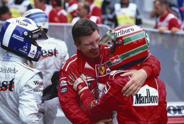 1999 Austrian Grand Prix. A1 Ring, Zeltweg, Austria. 23-25 July 1999. Eddie Irvine (Ferrari) celebrates his 1st position with Ross Brawn in parc ferme. David Coulthard (McLaren Mercedes) 2nd position, looks on. Ref-99 AUT 02. World Copyright - LAT Photographic