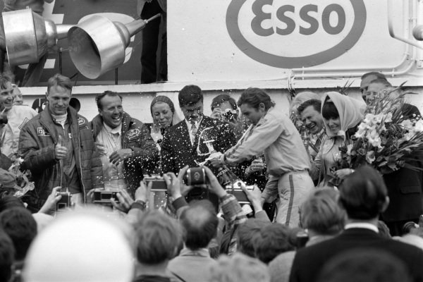 Dan Gurney and A.J. Foyt, 1st position, look on as 2.0 class winner Jo Siffert sprays champagne on the podium.