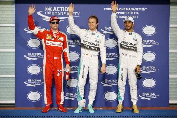 Yas Marina Circuit, Abu Dhabi, United Arab Emirates. Saturday 28 November 2015. Nico Rosberg, Mercedes AMG celebrates with Lewis Hamilton, Mercedes AMG and Kimi Raikkonen, Ferrari after taking Pole Position. World Copyright: Glenn Dunbar/LAT Photographic. ref: Digital Image _W2Q8871