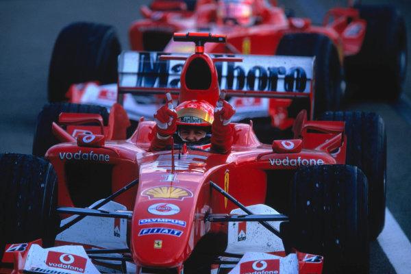 2004 Hungarian Grand Prix Hungaroring, Hungary. 13th - 15th August. Michael Schumacher, Ferrari F2004 celebrates his win as he comes into parc - ferme followed by team mate Rubens Barrichello, Ferrari F2004.World Copyright:Michael Cooper/LAT Photographic Ref:35mm Image:A18