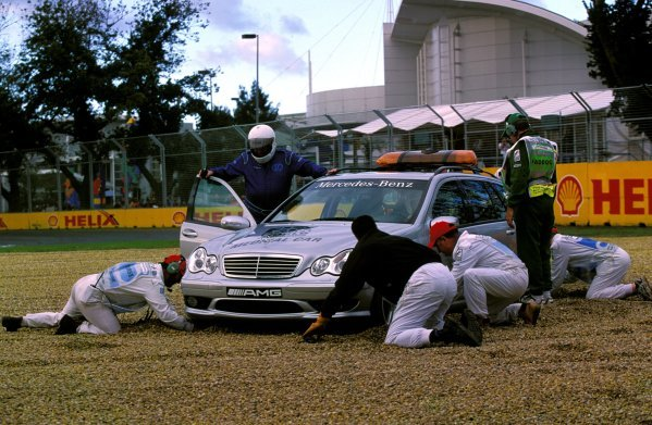 Professor Sid Watkins (GBR), looks on as marshals try to dig out the medical car that left the track and was stranded in the gravel trap. Australian Grand Prix, Rd1, Melbourne, Australia, 9 March 2003. BEST IMAGE