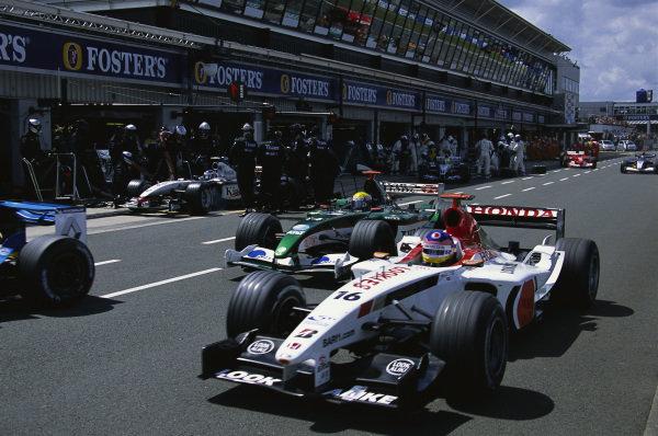 A group of cars going through the pitlane, including Jacques Villeneuve, BAR 005 Honda, Mark Webber, Jaguar R4 Cosworth, and Kimi Räikkönen, McLaren MP4-17D Mercedes. The latter is making a pitstop.