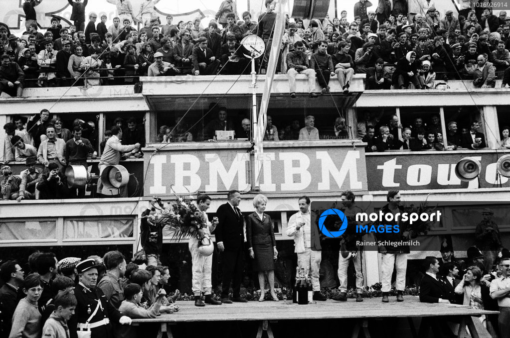 Overall winners Bruce McLaren and Colin Davis celebrate on the podium with class winners and fellow Ford drivers Jo Siffert and Chris Amon, and Henry Ford II.