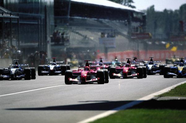 Michael Schumacher, Ferrari F2003-GA, leads Juan Pablo Montoya, Williams FW25 BMW, Rubens Barrichello, Ferrari F2003-GA, and Jarno Trulli, Renault R23B, at the start.