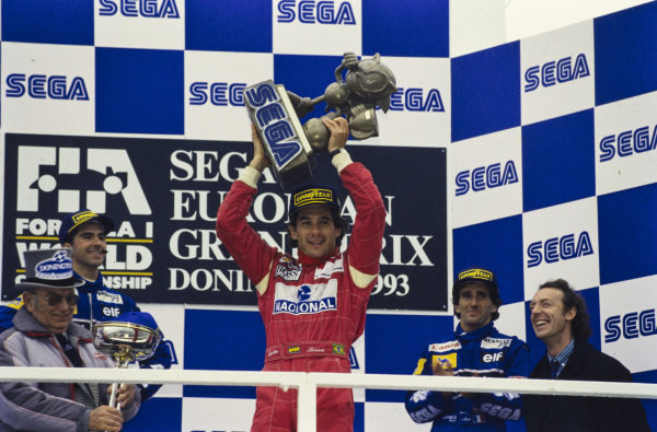 Ayrton Senna, 1st position, holds the Sega Sonic the Hedgehog trophy aloft on the podium. Damon Hill, 2nd position, Alain Prost, 3rd position, and circuit owner Tom Wheatcroft are all also present.