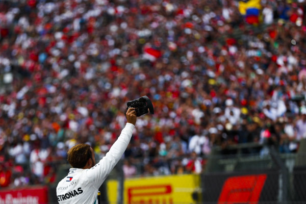 Lewis Hamilton, Mercedes AMG F1, holds his steering wheel aloft after securing his 5th world drivers title