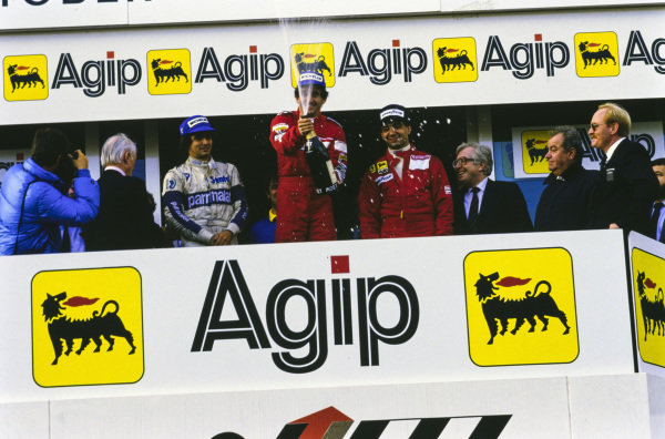 Alain Prost, 1st position, sprays champagne on the podium. Either side are Michele Alboreto, 2nd position, and Nelson Piquet, 3rd position.
