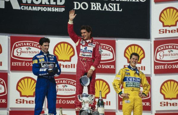 Ayrton Senna, 1st position, celebrates on the podium alongside Damon Hill, 2nd position, and Michael Schumacher, 3rd position.