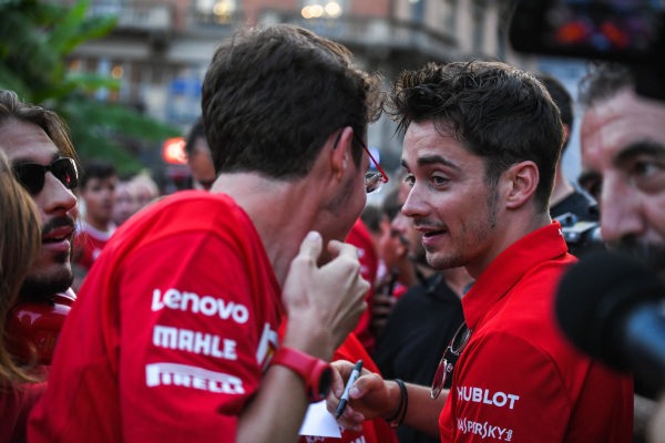 Charles Leclerc, Ferrari talks to a fan as he signs an autograph