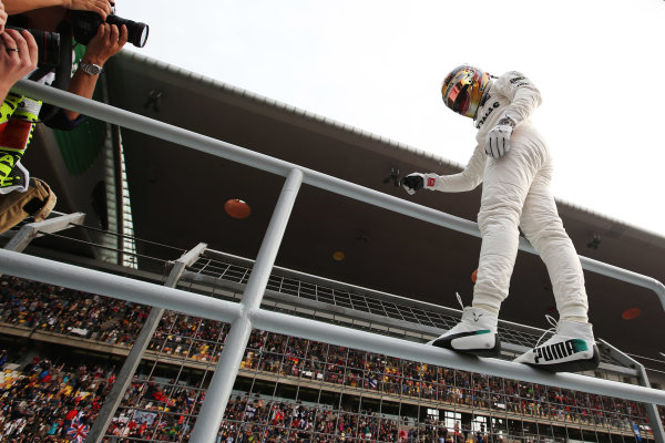 Shanghai International Circuit, Shanghai, China.  Saturday 08 April 2017.  Lewis Hamilton, Mercedes AMG, climbs a fence to celebrate pole position. World Copyright: Charles Coates/LAT Images  ref: Digital Image AN7T9019