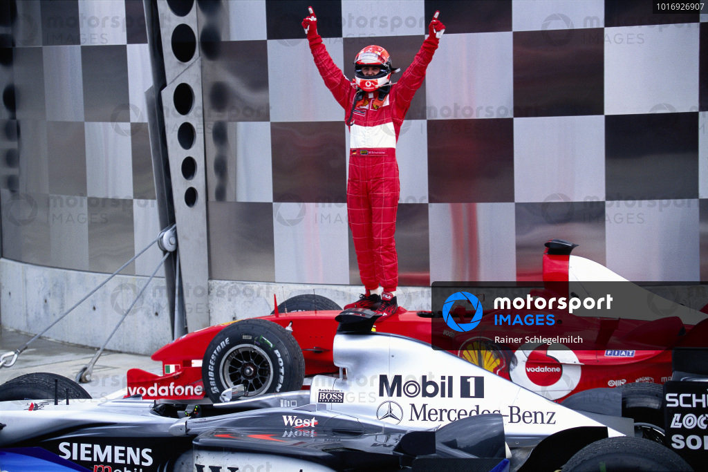 Michael Schumacher celebrates victory on top of his Ferrari F2003-GA.