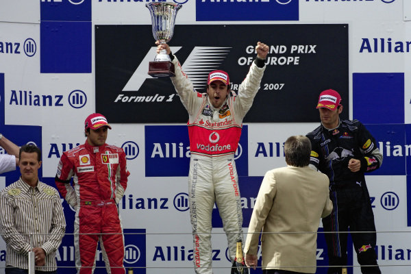 Fernando Alonso raises his trophy high as he celebrates victory on the podium. Felipe Massa, 2nd position, and Mark Webber, 3rd position, await their trophies as Michael Schumacher joins them in the presentation.