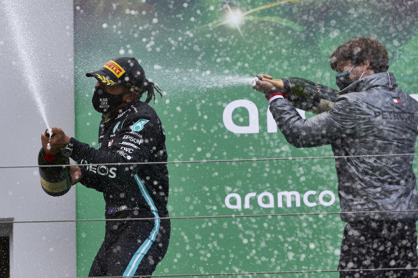 Lewis Hamilton, Mercedes-AMG Petronas F1, 1st position, and Steven Lord, Mercedes, spray Champagne on the podium
