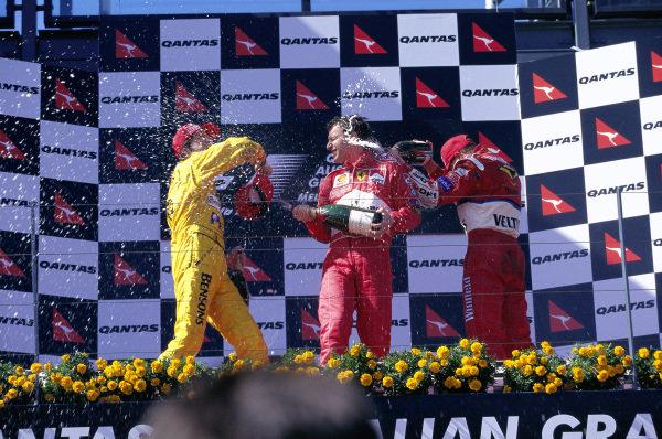 Heinz-Harald Frentzen, 2nd position, Eddie Irvine, 1st position, and Ralf Schumcher, 3rd position, celebrate on the podium.
