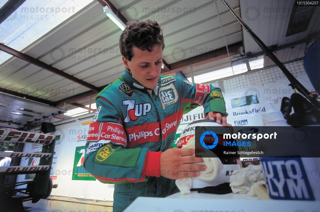 Michael Schumacher cleans his helmet visor in the garage.