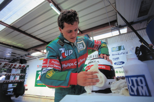 Michael Schumacher cleans his helmet visor in the garage.