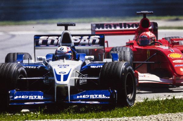 Juan Pablo Montoya, Williams FW23 BMW, locks up under braking, forcing himself and Michael Schumacher, Ferrari F2001, wide onto the grass.