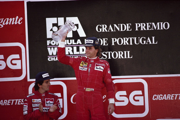 Gerhard Berger, 1st position, celebrates on the podium with Alain Prost, 2nd position.