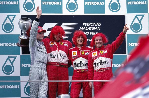 Michael Schumacher, Ferrari, 1st position, David Coulthard, McLaren, 2nd position, Rubens Barrichello, Ferrari, 3rd position, and Ross Brawn on the podium.