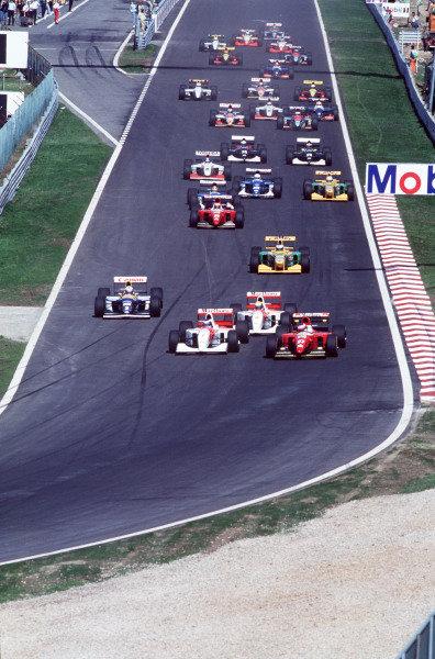 Jean Alesi, Ferrari F93A, battles with Mika Häkkinen, McLaren MP4-8 Ford, into the first corner at the start, as Ayrton Senna, McLaren MP4-8 Ford, leads Alain Prost, Williams FW15C Renault, and Michael Schumacher, Benetton B193B Ford.