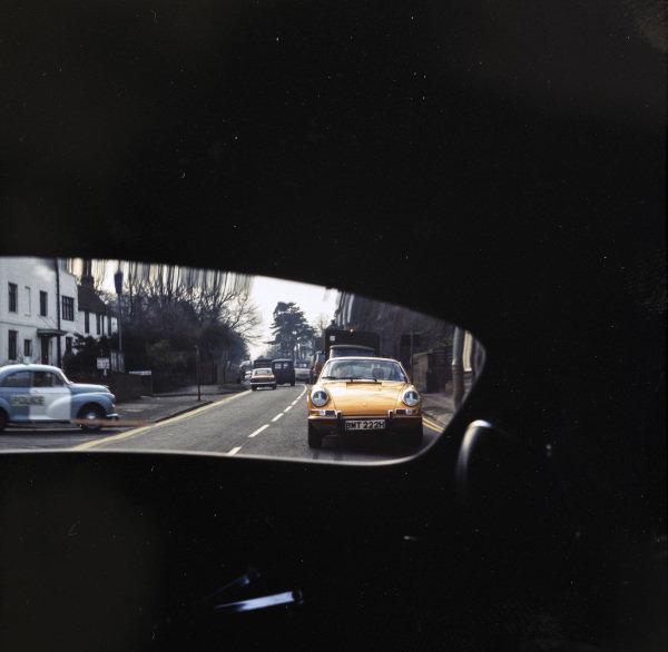 """A Morris Minor """"Panda"""" car observes the passage of a Porsche 911 as seen from an E type Jaguar."""