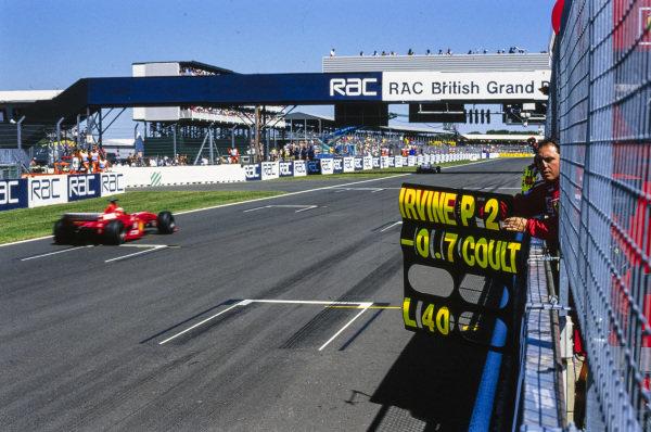 Pit board deployed as Eddie Irvine, Ferrari F399, passes.