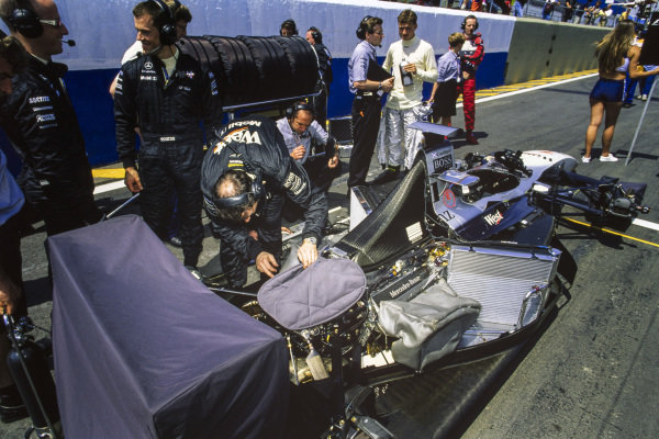 David Coulthard beside his McLaren MP4-13 Mercedes as engineers work on the exposed car.